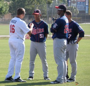 Beloit manager Nelson Prada chats with Eddie Rosario, Miguel Sano and Daniel Ortiz