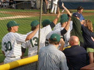 Young fans exchange high fives with Snappers players as they walk from their outfield pregame stretching to their dugout