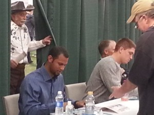 "Twins prospects Aaron Hicks and Kyle Gibson at the autograph station, with Twins Clubhouse manager Wayne ""Big Fella"" Hattaway peeking in from behind the curtain"