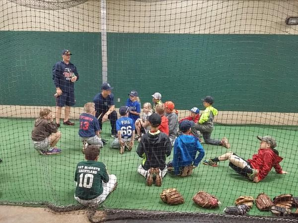 Cam Booser and Trey Vavra talking baseball with campers in the indoor batting cage