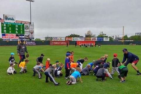 Blake Schmit and Randy LeBlanc teaching campers proper fielding position