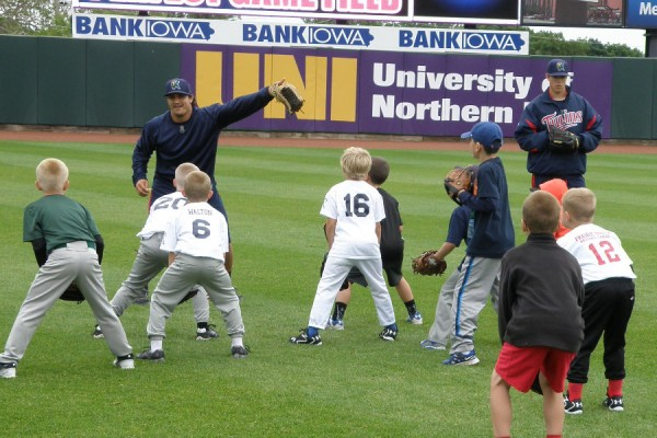 TJ White and Trevor Hildenberger working with a group of outfielders