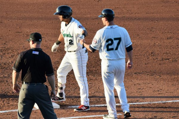 Luis Arraez had a pair of hits for the West squad. Here he's fist-bumped by Kernels coach Brian Dinkelman.